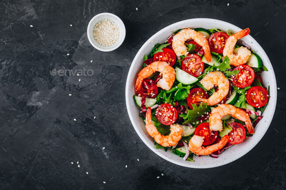 Shrimp salad with fresh green lettuce and radicchio leaves, cucumbers, tomatoes and sesame seeds. - Stock Photo - Images
