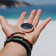 Outstretched hand holding black metal compass against white sandy beach and blue sea. Find your way - PhotoDune Item for Sale