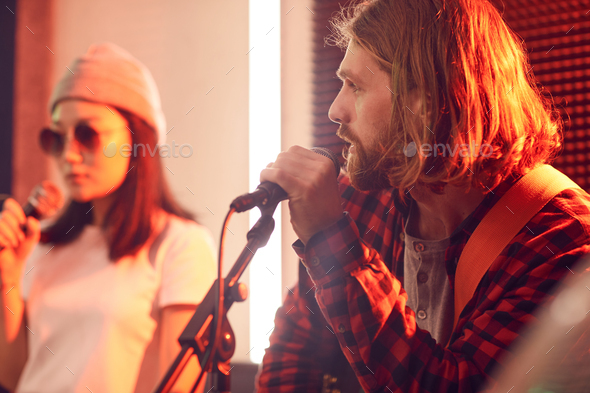 Handsome Young Man Singing with Band in Studio - Stock Photo - Images