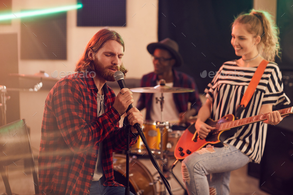 Bearded Young Man Singing to Microphone with Band in Studio - Stock Photo - Images