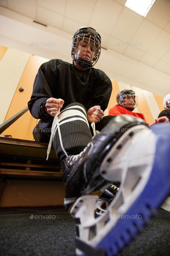 Female Hockey Player Putting on Skates - Stock Photo - Images
