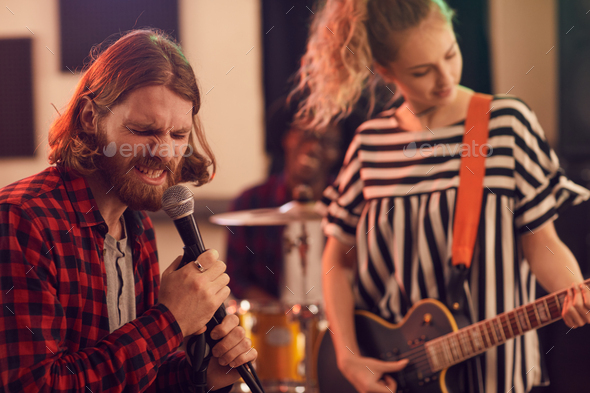 Bearded Young Man Singing to Microphone with Rock Band - Stock Photo - Images