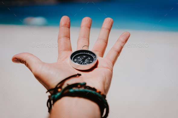 Open palm with stretched fingers holding black metal compass against white sandy beach. Find your - Stock Photo - Images