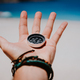 Open palm with stretched fingers holding black metal compass against white sandy beach. Find your - PhotoDune Item for Sale