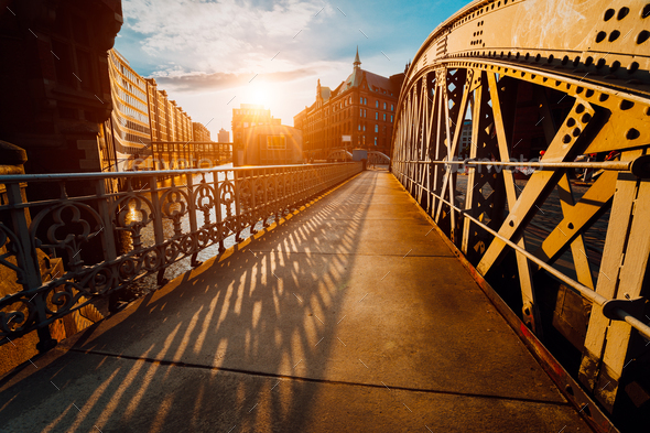 Bridge Arch with rivets in the Speicherstadt of Hamburg during sunset golden hour with sunset light - Stock Photo - Images