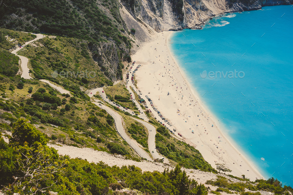 Serpentine road to famous Myrtos Beach with many tourists, Kefalonia, Greece - Stock Photo - Images