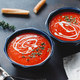 Two portions of red tomato cream soup in bowls with spices. - PhotoDune Item for Sale