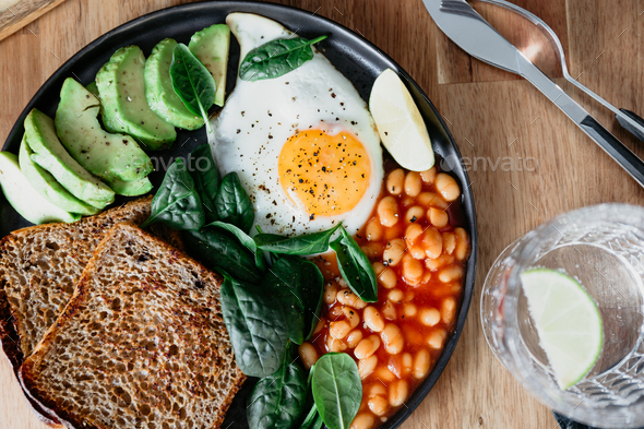 Fried egg, avocado, toasts, beans and fresh spinach - Stock Photo - Images