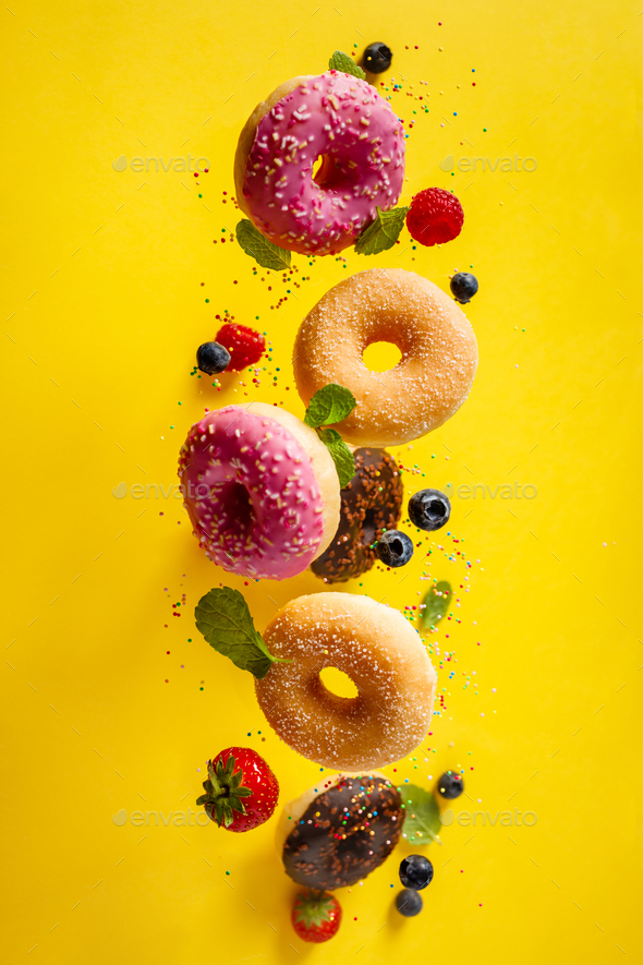 Various decorated doughnuts with sprinkles and berries in motion falling on yelloy background - Stock Photo - Images