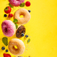 Various decorated doughnuts with sprinkles and berries in motion falling on yelloy background - PhotoDune Item for Sale