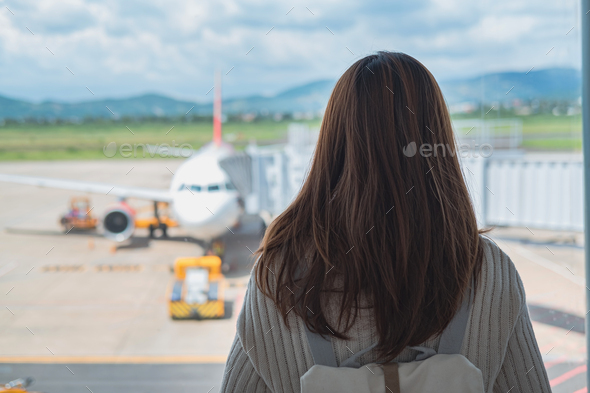 Young woman traveler looking at the airplane at the airport, Travel concept - Stock Photo - Images