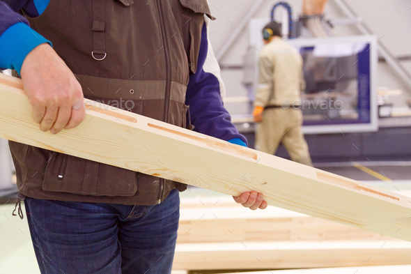 Carpenter with a planed board in his hands, a close-up of a worker at the enterprise. - Stock Photo - Images