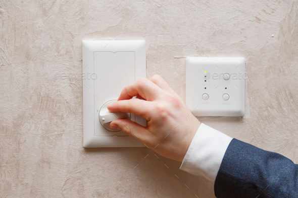Man regulating temperature on air conditioning controller thermostat on the wall - Stock Photo - Images