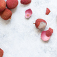 Fresh litchi fruits on a white table - PhotoDune Item for Sale