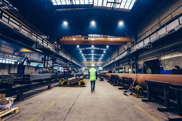 Engineer walking in large factory, blue-collar workers at work. - Stock Photo - Images