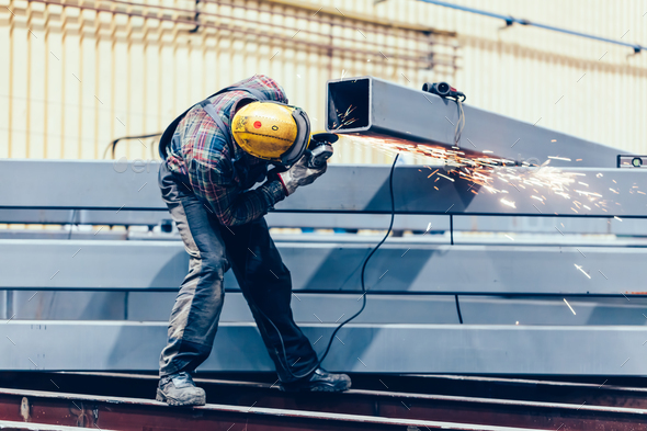 Worker grinding a steel profile in factory. - Stock Photo - Images