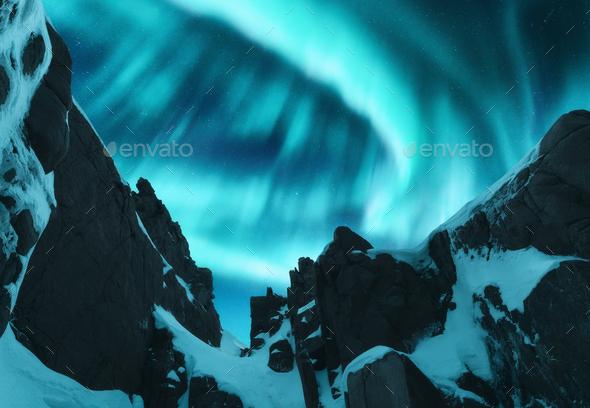 Aurora borealis above the snow covered mountain peak - Stock Photo - Images