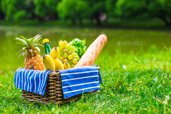 Picnic setting with white wine, pears, fruits, bread - Stock Photo - Images