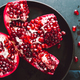 Top down view on a ripe pomegranate in a black plate on a dark background - PhotoDune Item for Sale