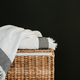 White cotton towels on a rattan box against black wall in a laundry. - PhotoDune Item for Sale