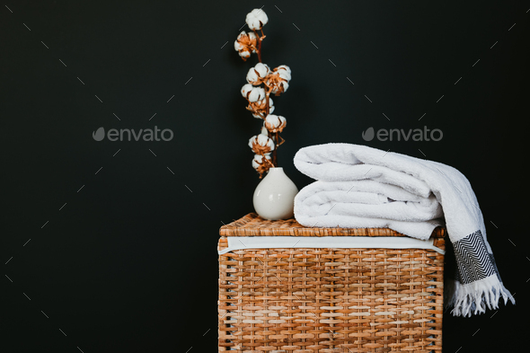 White cotton towels on a rattan box against black wall in a laundry. - Stock Photo - Images