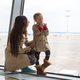 Mother and little daughter looking out the window at airport terminal - PhotoDune Item for Sale