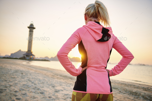 Rear view of sporty woman on the beach - Stock Photo - Images