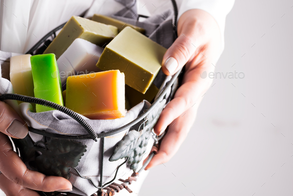 A woman holding handcrafted olive oil soap in basket . Handmade zero waste concept - Stock Photo - Images