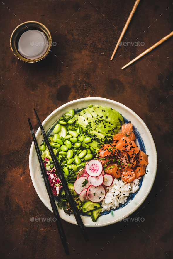 Hawaiian salmon poke bowl with vegetables, greens, rice, soy sauce - Stock Photo - Images
