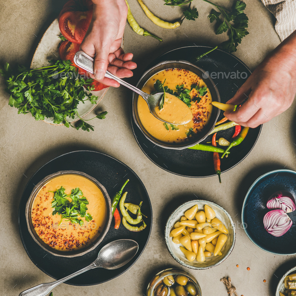 Man eating turkish traditional lentil soup Mercimek with pickled peppers - Stock Photo - Images
