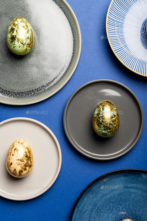 Different Plates with Easter Eggs of pastel colors on blue background - Stock Photo - Images
