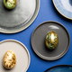 Different Plates with Easter Eggs of pastel colors on blue background - PhotoDune Item for Sale