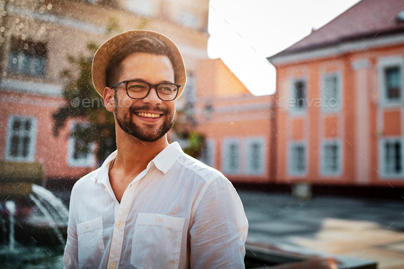 Portrait of handsome young man smiling outdoors - Stock Photo - Images