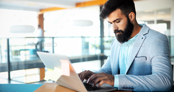 Professional businessman working on laptop in office - Stock Photo - Images