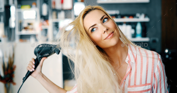 Smiling young woman blow drying hair - Stock Photo - Images