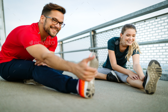 Fitness, sport, training and lifestyle concept. Fit couple friends stretching outdoors - Stock Photo - Images