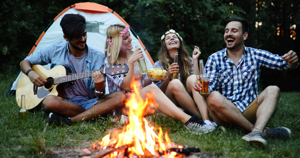 Group of friends camping and sitting around camp fire - Stock Photo - Images