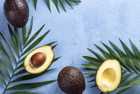 Half and whole avocado and palm leaves - Stock Photo - Images
