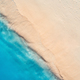 Aerial view of clear blue sea with waves and empty sandy beach - PhotoDune Item for Sale