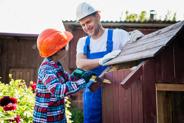 Handsome teenage carpenter and his father in protective glasses are smiling while working with wood - Stock Photo - Images
