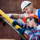 Turning their visions into reality. Cheerful young male carpenter embracing his son while measuring - PhotoDune Item for Sale