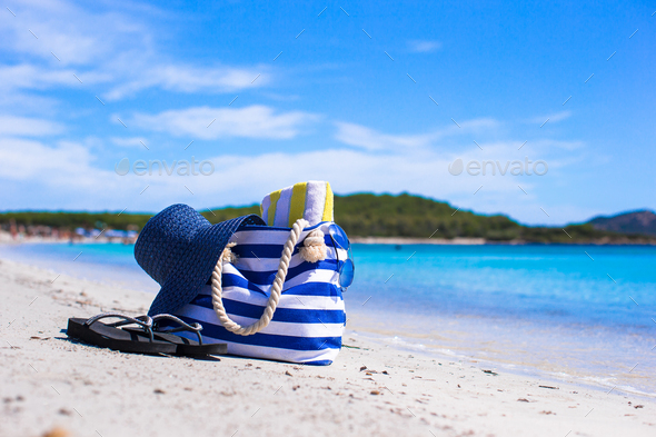 Blue bag, straw hat, flip flops and towel on white tropical beach - Stock Photo - Images