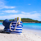 Blue bag, straw hat, flip flops and towel on white tropical beach - PhotoDune Item for Sale