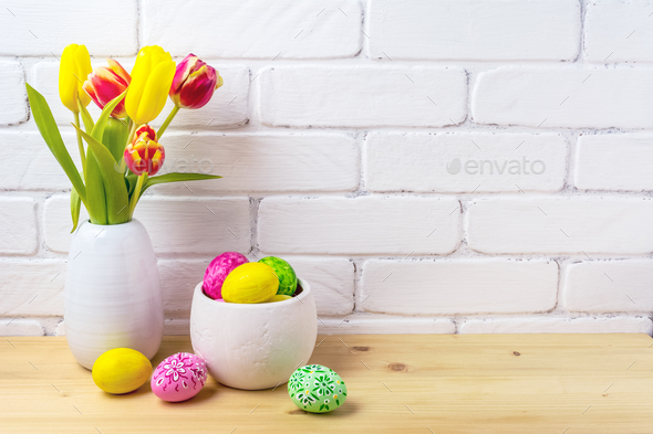 Easter rustic arrangement with eggs, red and yellow tulips - Stock Photo - Images