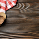 Red checkered napkin and wooden utencils on brown wooden kitchen table with copy-space. Top view - PhotoDune Item for Sale