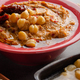 Hummus topped with beans, sun dried tomatoes and olive oil on kitchen table - PhotoDune Item for Sale