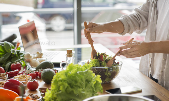 Woman mixing delicious superfood salad ingredients in the kitchen - Stock Photo - Images