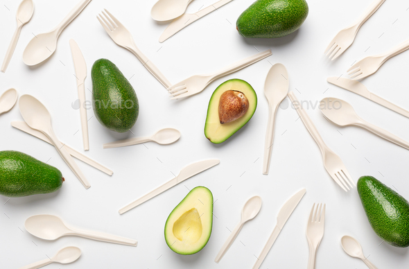 Halves of avocado and eco disposable tableware isolated on white - Stock Photo - Images