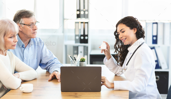 Mexican doctor showing diagnosis to elderly couple - Stock Photo - Images