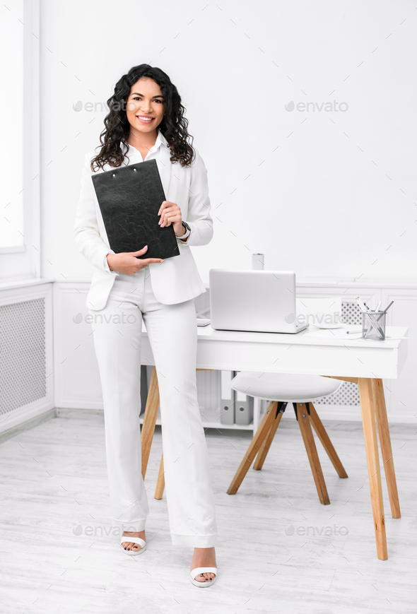 Full length image of latin woman with clipboard - Stock Photo - Images